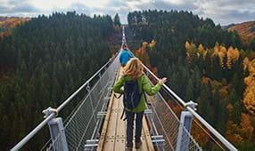 Hikers Walking Across a Forest Bridge in Fall