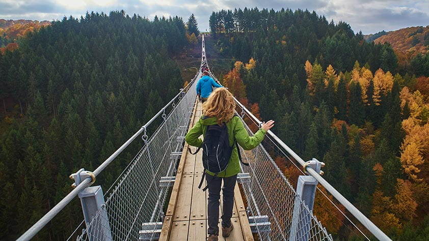 Hikers Walking Across a Forest Bridge in Fall - Fall Vacation Ideas
