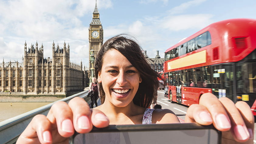 Young woman taking a selfie with her smartphone in front of the Houses of Parliament and Big Ben