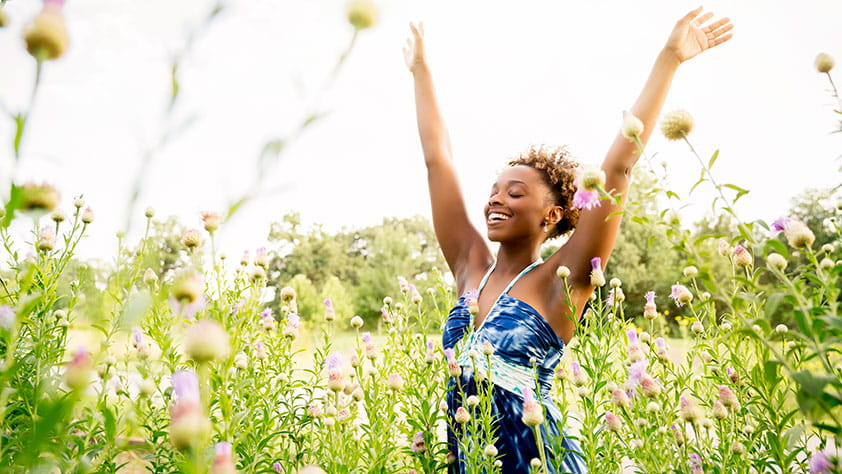 Smiling woman with arms raised in field of wildflowers