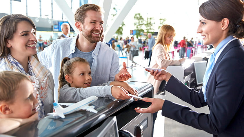 Customer service representative helping a family check in at the airport ticket counter