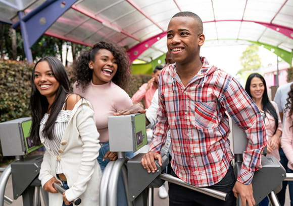 Group of young people arriving at an amusement park and looking very happy