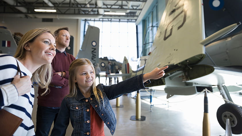 Family looking at an airplane in a museum