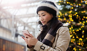 Woman on Smartphone Standing in Front of Christmas Tree Display