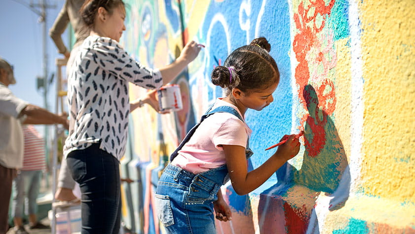Girl volunteers painting a vibrant mural on a sunny wall