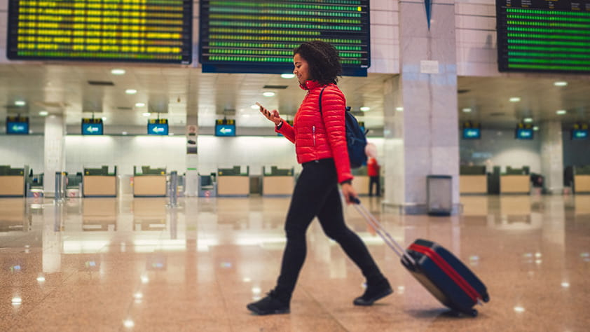 Woman walking through an airport with her wheeled suitcase