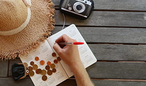 Overhead shot of a camera, straw hat and a man's hand marking dates in a calendar on a wooden table