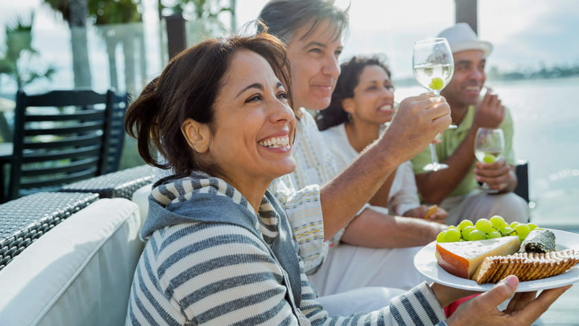 Smiling woman holding a cheese plate with friends on a patio
