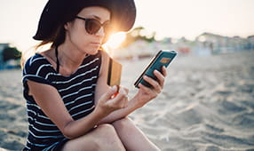 Woman on Smartphone on Beach