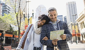 Couple Walking Through City Reviewing a Map