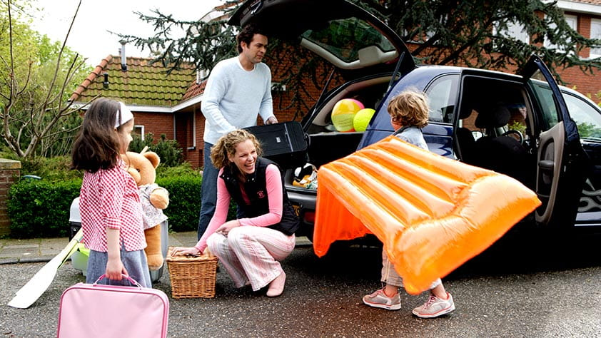 Family of four packing their car for a summer trip