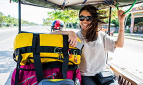 Woman on vacation riding in a rickshaw with her luggage