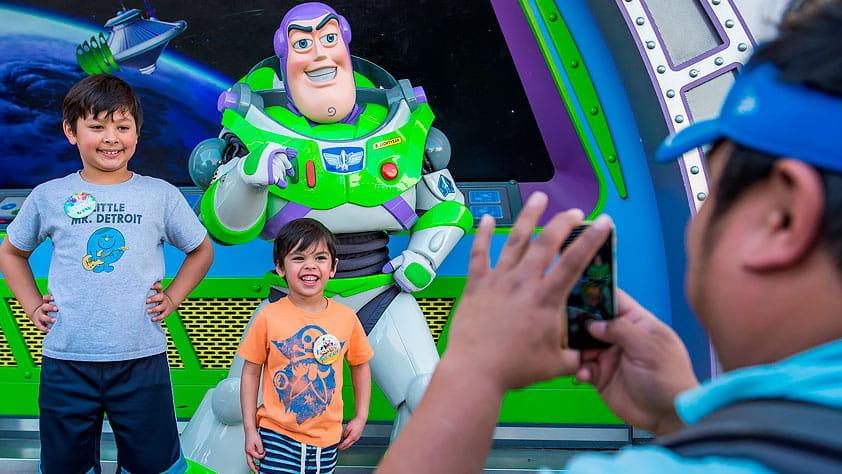 Father taking a picture of this two boys with Buzz Lightyear. Buzz Lightyear photo by Matt Stroshane / Walt Disney World