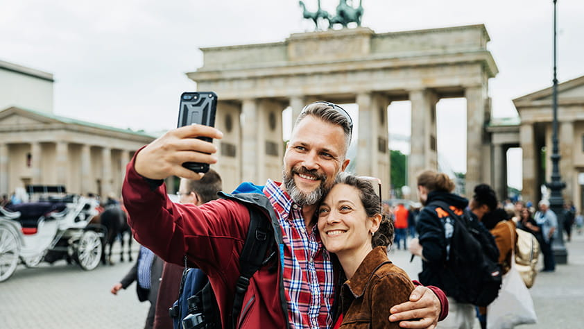 Make This the Year Your Plan Your Dream Trip - Couple Taking A Selfie Together on Front of Brandenburg Gate in Berlin
