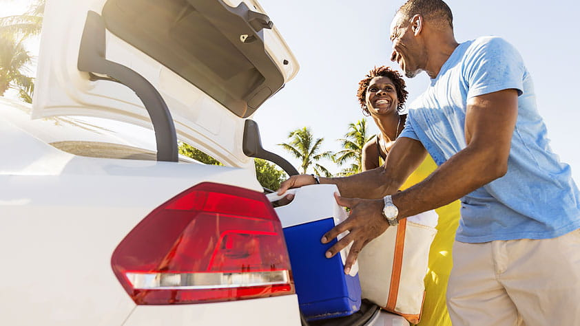 NEA Members Share Future Travel Plans - Couple Loading a Cooler into the Trunk of Their Car