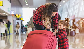 Mother and Daughter with a Red Suitcase at the Airport