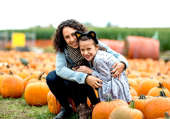 Mother and daughter sit on pumpkins at a pumpkin farm