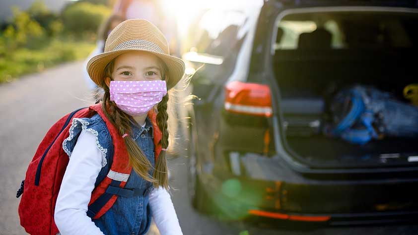 Young Girl Wearing a Backpack and Face Mask Standing Next to the Family Car