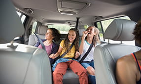Three Girls Laughing in Back of Car