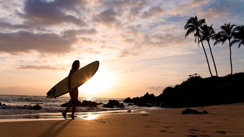 Silhouette of a female surfer at sunset on tropical beach