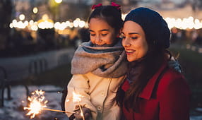 Mother and daughter holding sparklers at a winter event