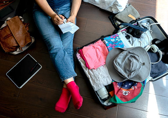 Woman sitting on the floor with her open suitcase writing in a notepad