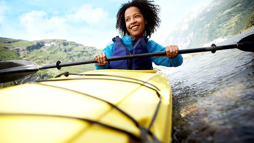 Woman in a blue jacket and life vest paddling a bright yellow kayak