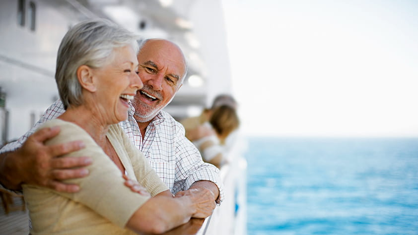 Happy older couple looking off the side of a cruise ship