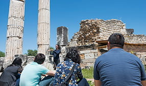 Guide explaining to tourists the ruins of stone columns and structures
