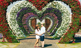 Couple holding hands while standing under a heart-shaped sculpture made of live flowers