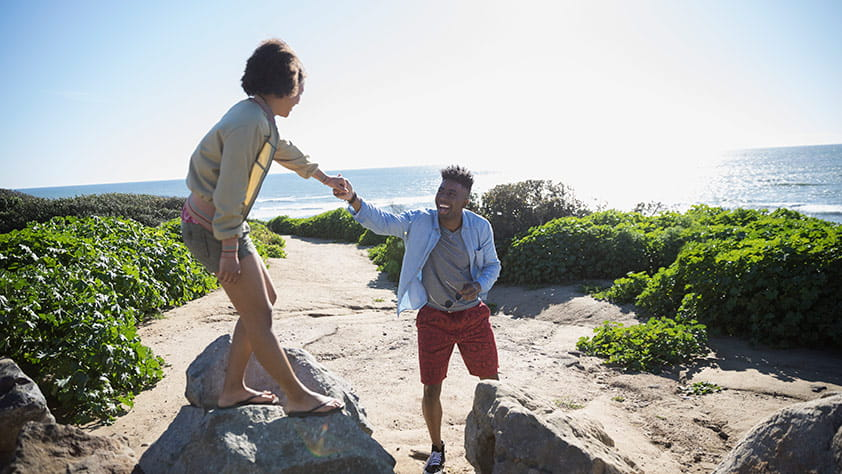 Spring Break Destinations for Grownups - Couple Walking on Large Rocks at the Beach