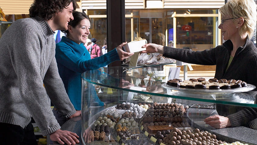 Woman behind a counter in a chocolate shop handing a couple a box of chocolates