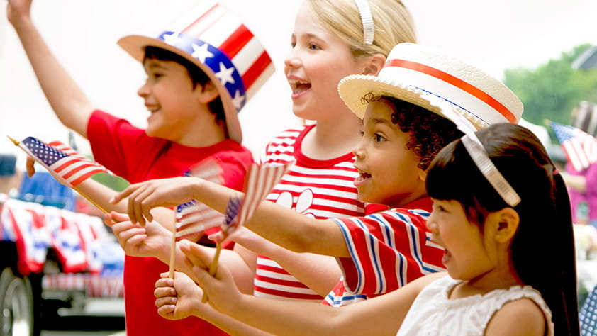 Children dressed in red, white and blue cheering at fourth of July celebration