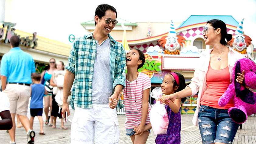 Family walking through the games section of an amusement park
