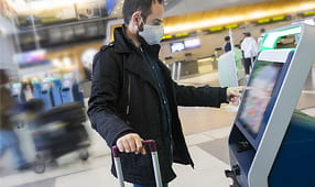 Young Man Wearing a Face Mask Using Self Check-In at the Airport