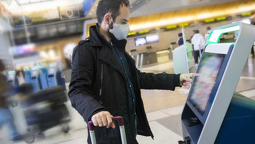 Tips for Holiday Travel During Coronavirus - Young Man Wearing a Face Mask Using Self Check-In at the Airport