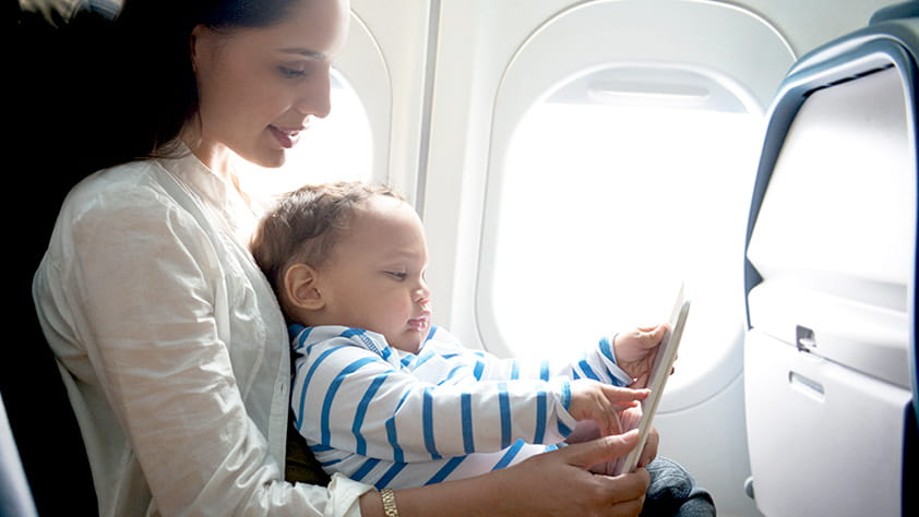 Mother and toddler son sitting in an airplane using a digital tablet