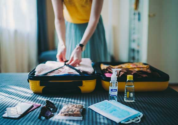 Woman Packing Suitcase for a Trip Including Face Masks and Hand Sanitizer