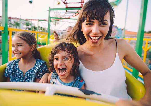 Young Son and Daughter with Their Mother on a Roller Coaster Ride