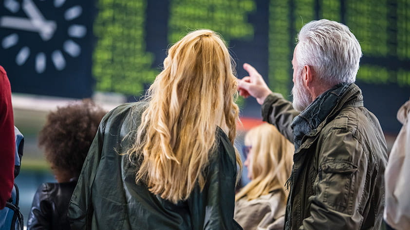 Couple Looking at Train Schedule at Train Station