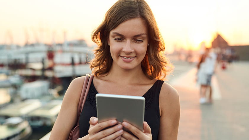 Woman Staring at Tablet on Dock at Sunset