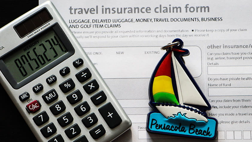 Close-up of a calculator, a key ring in the shape of a colorful sailboat and a travel insurance claim form