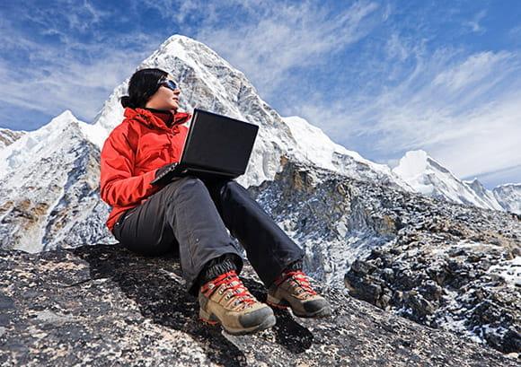 Woman with Laptop Wearing an Orange Parka Sitting on Mountain Rocks