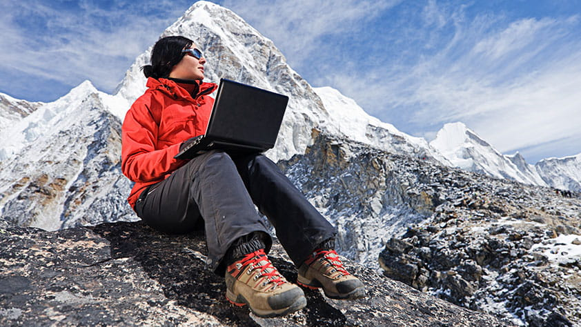 Grants for Educators - Woman with Laptop Wearing an Orange Parka Sitting on Mountain Rocks
