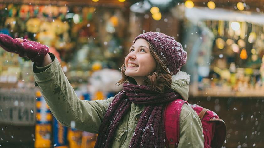 Smiley woman enjoying snow falling