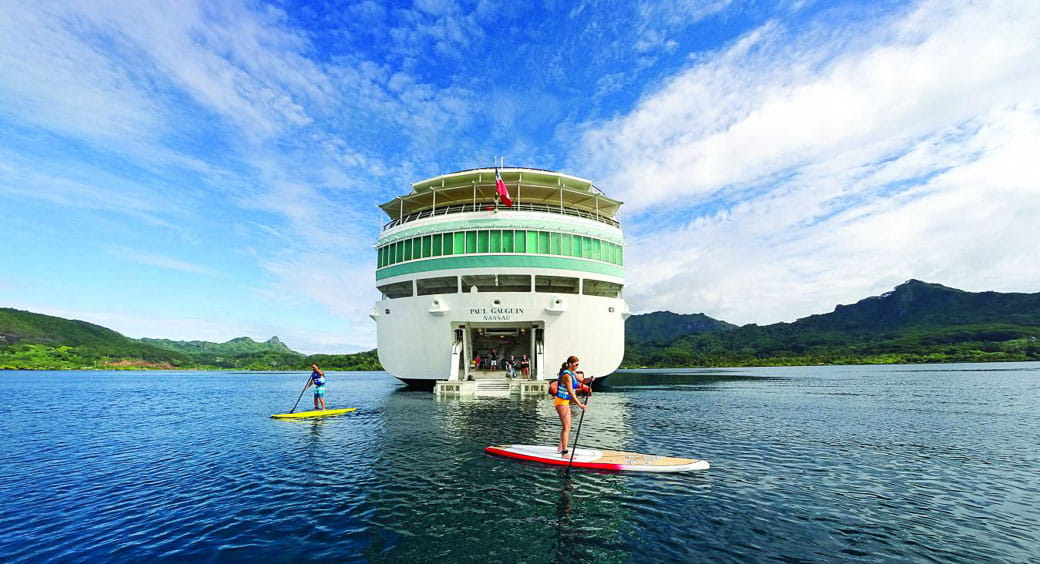 Two tourists paddleboarding in front of a cruise ship