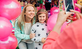 Mother Taking Photo with Daughter Holding Pink Balloons