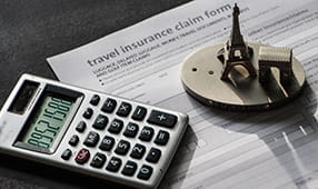 Close-up to travel insurance orm, calculator and eiffel tower miniature