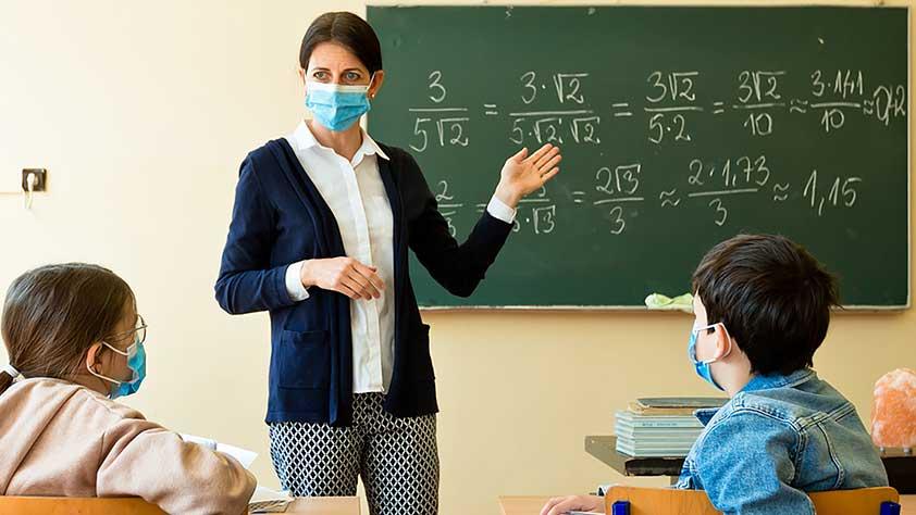 Female teacher wearing a mask teaching mathematics at school during Covid-19