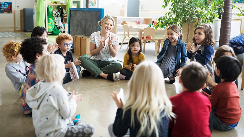Preschool teacher and students clapping in a circle on the floor in a classroom